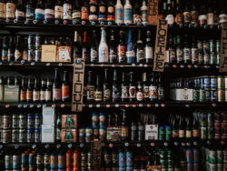 Many different beer bottles on shelves